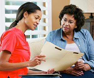 Hospice Patient Reviewing Care With Nurse