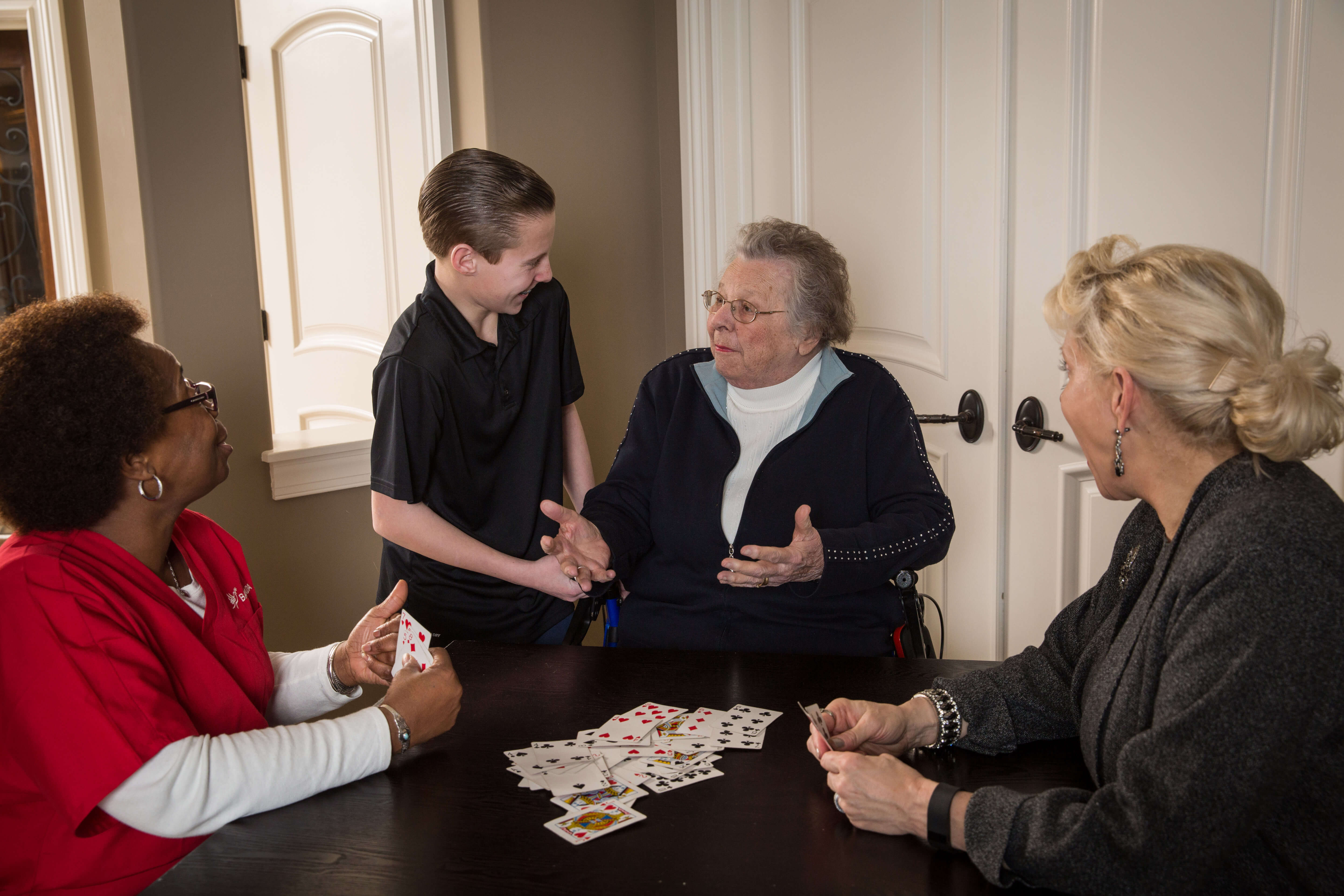 Aging parent, adult child, home health aide, and grandson playing cards