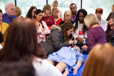 continuing education for nurses: BAYADA nurses peer over a dummy at BAYADA's Simulation Consortium 2018