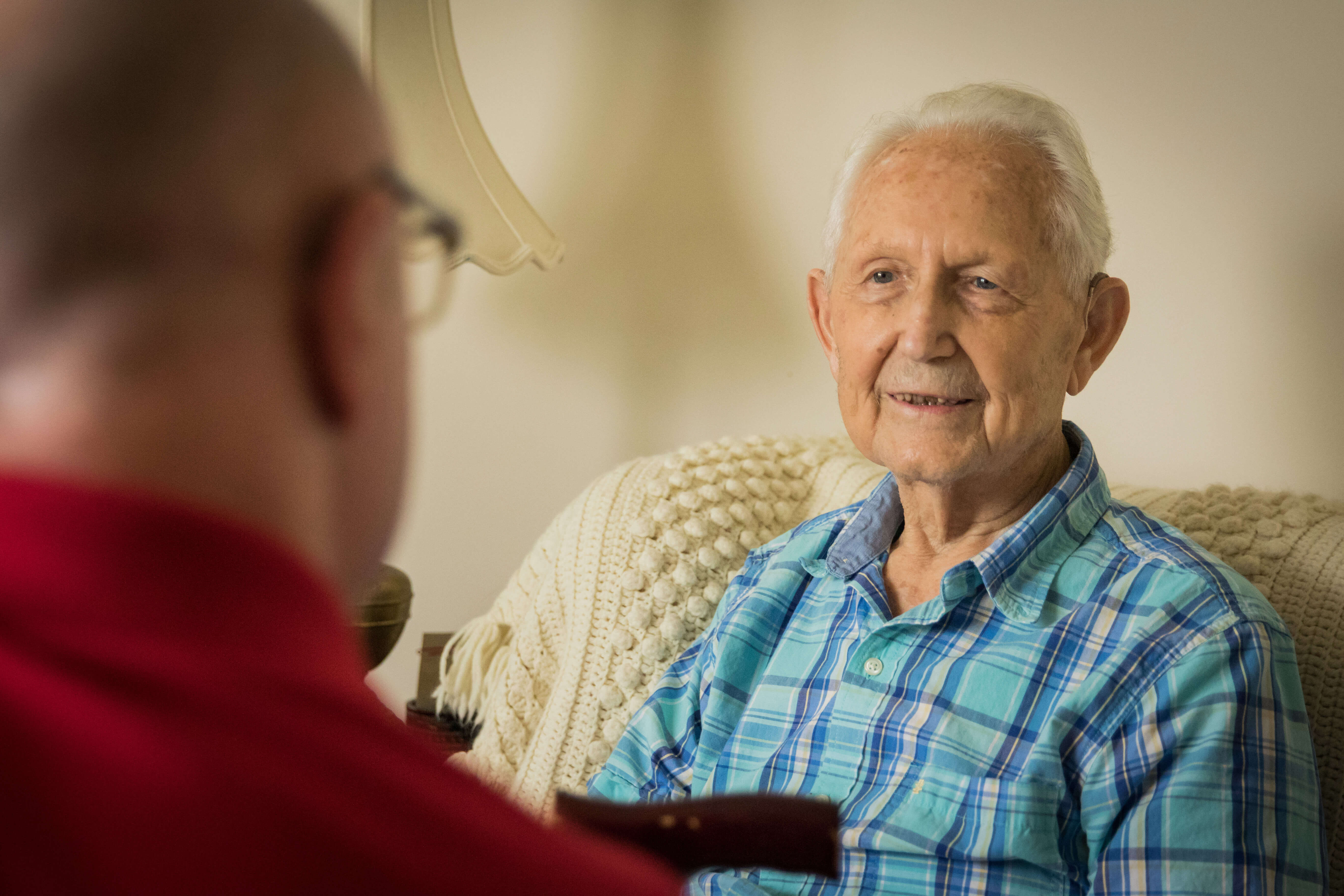 Home health social worker speaks to client, and client smiles.