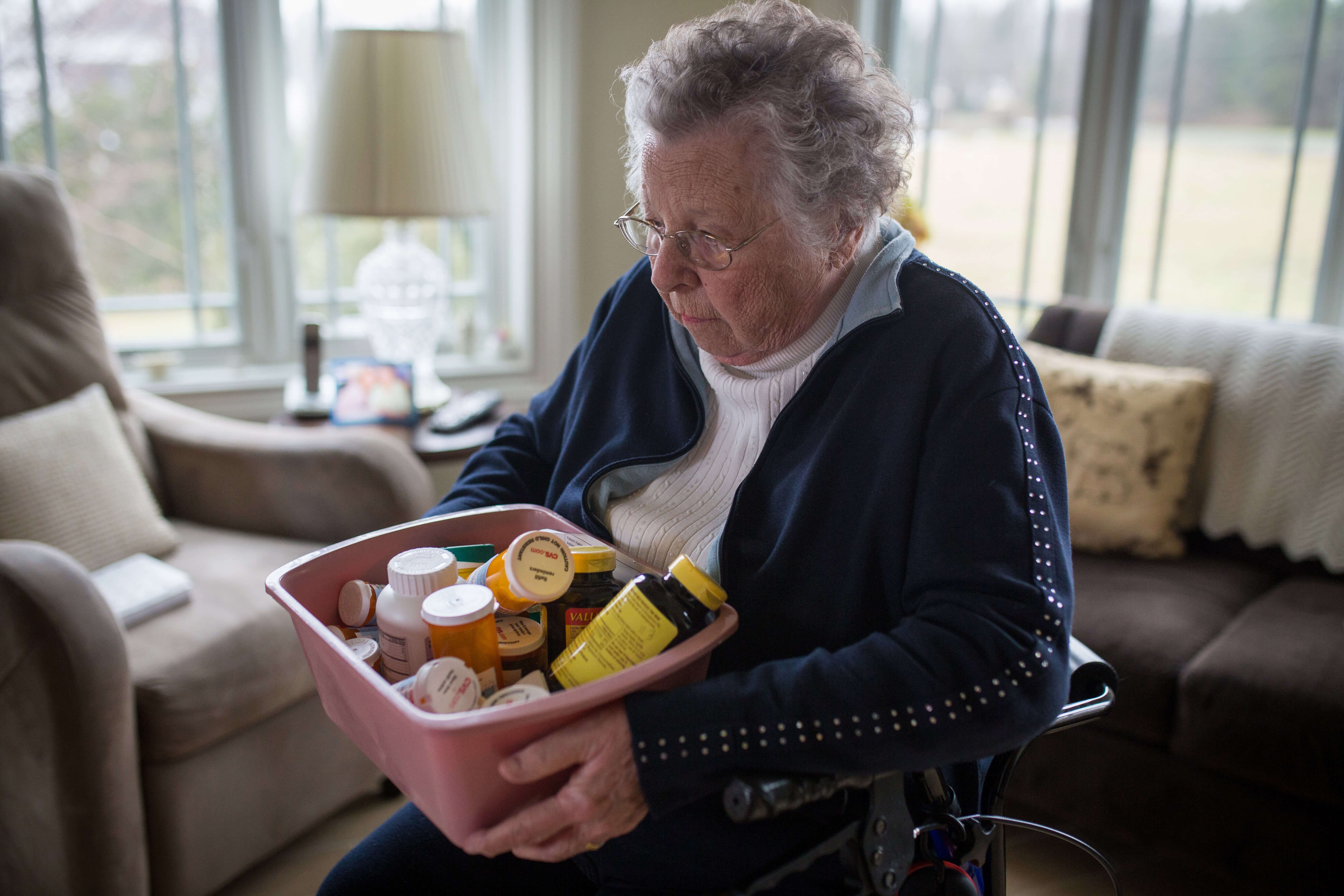 Senior woman holds box of medication in her arms; she needs medication management.