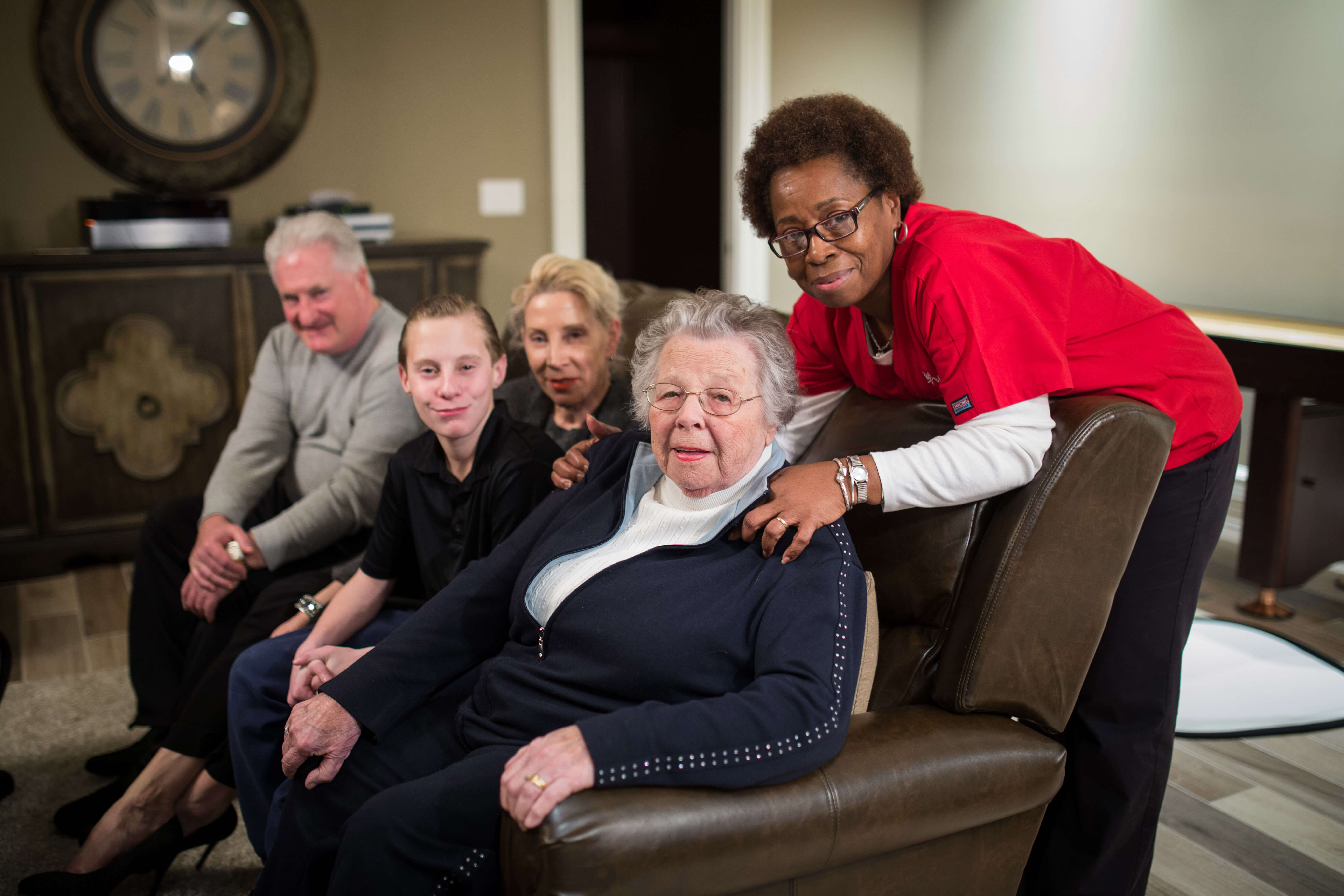 An aide who provides respite care to a senior poses with the senior and their family.