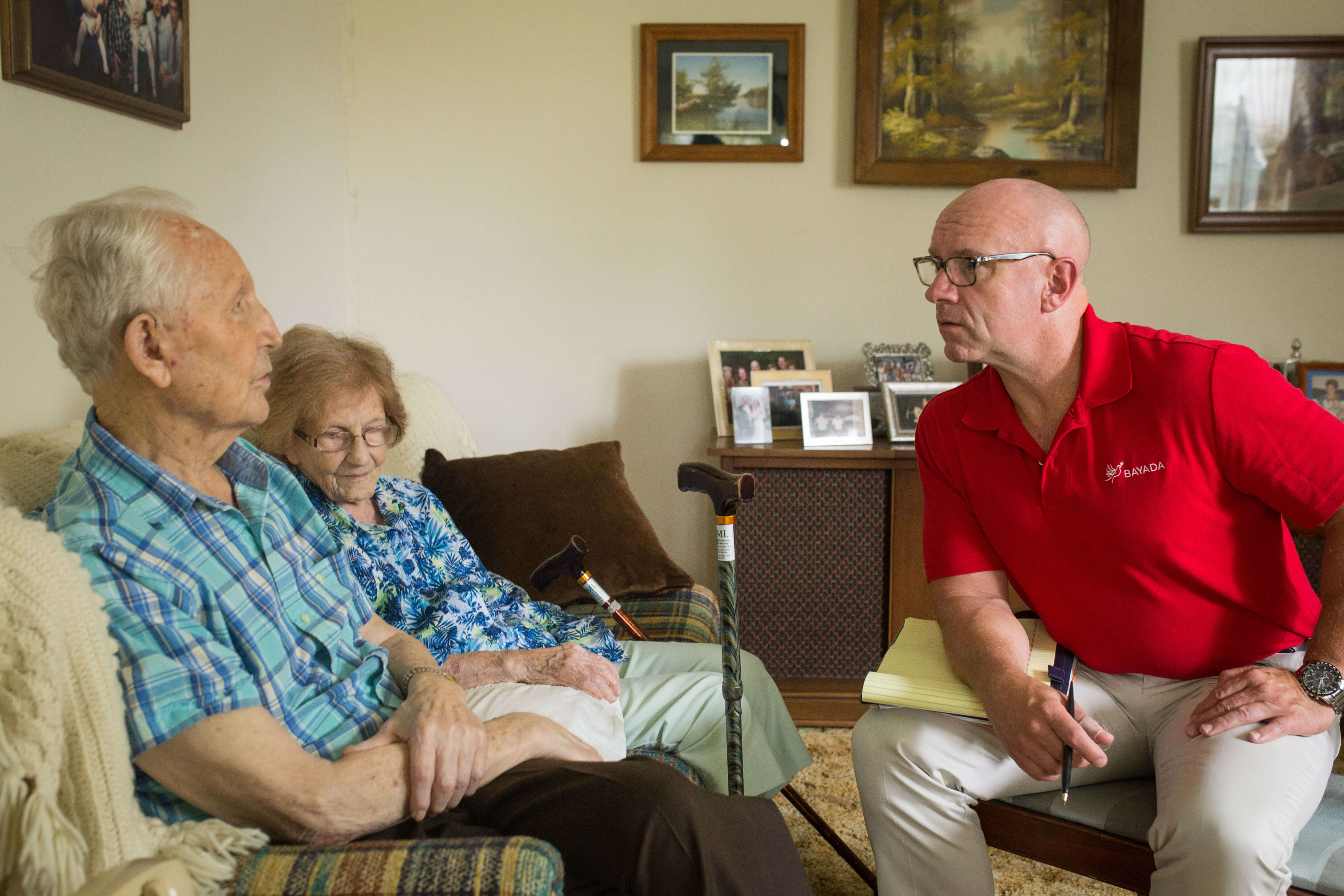 Stephen, a hospice social worker, speaks to his hospice client in his living room.