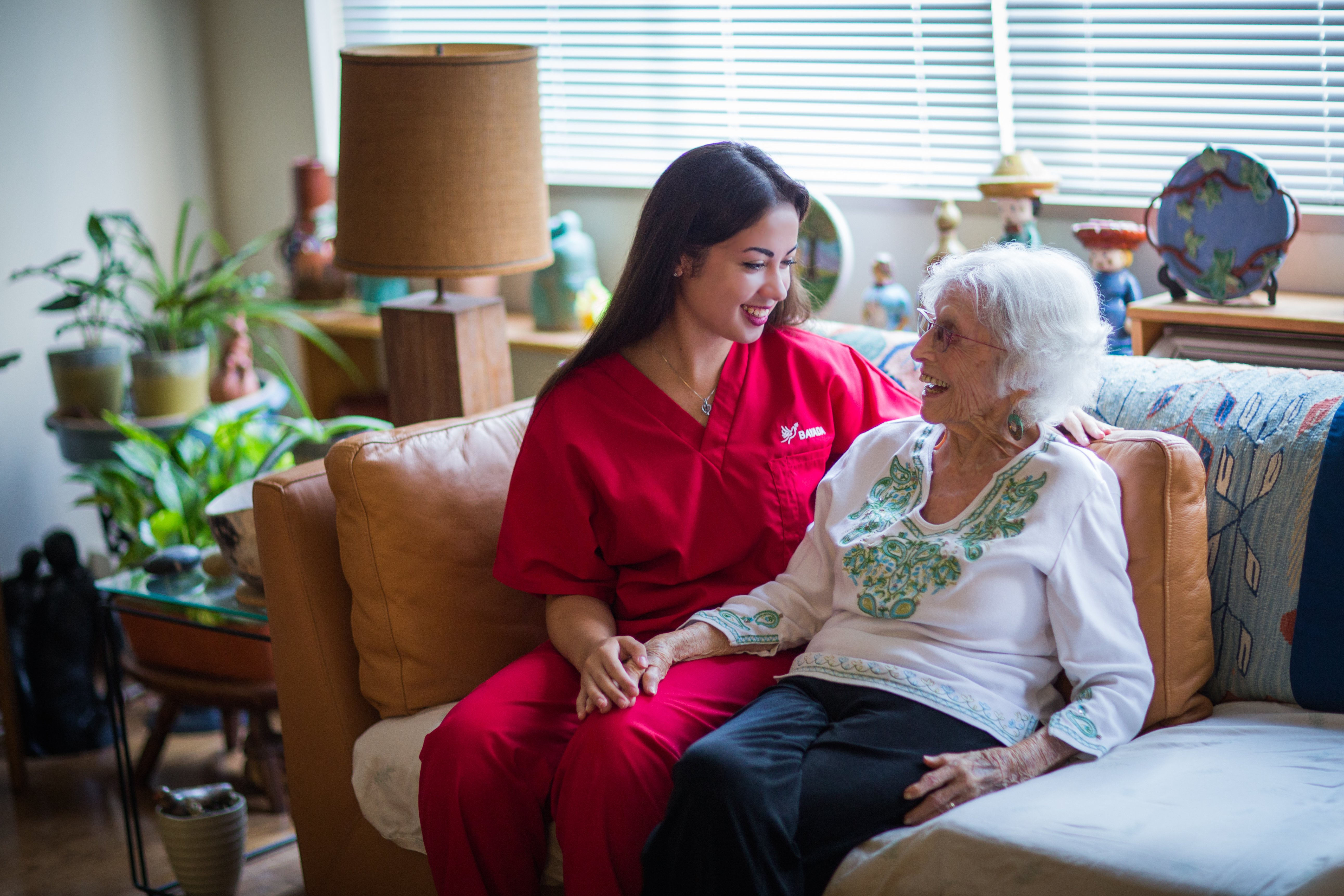 Home health aide sits on couch with her client.