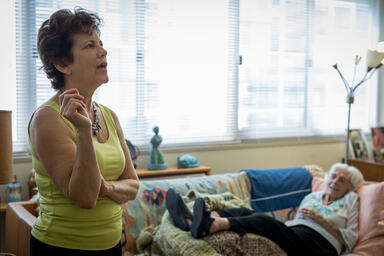 Caring for elderly parents: family caregiver speaks while parent is in background