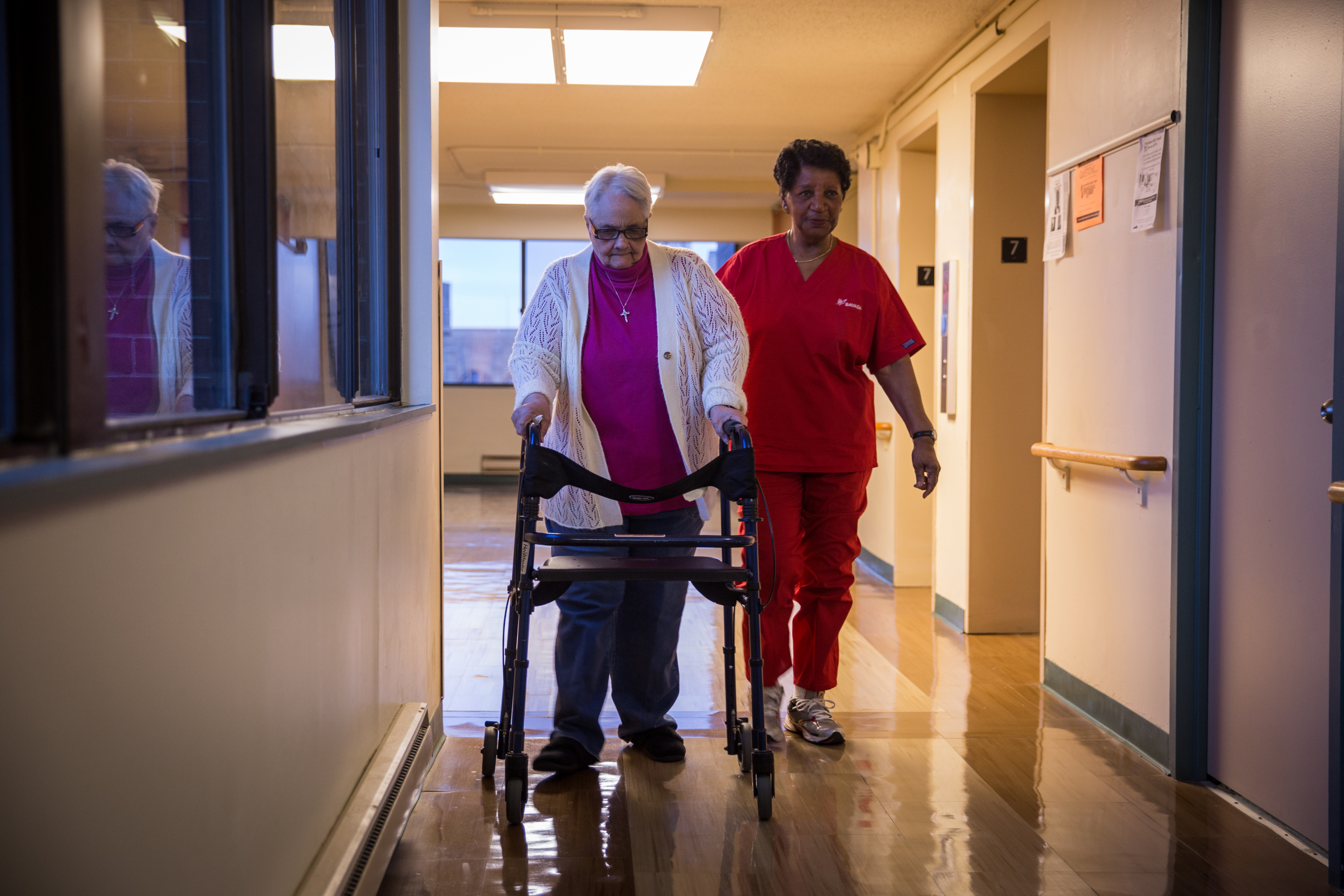 A home health aide leads her patient down a hallway.